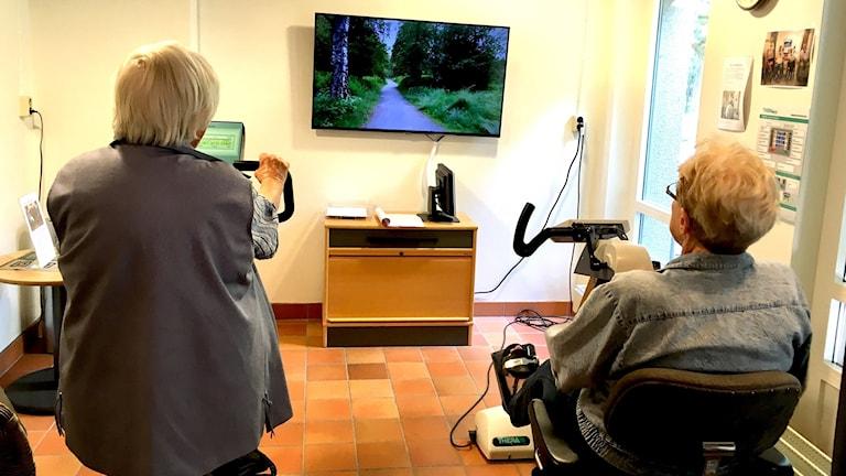 Pensionärer på två cyklar med en tv i bakgrunden. Annika Ström/Sveriges Radio.