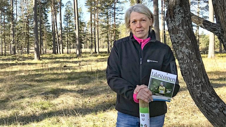 Mimmi Adolfsson står vid en orienteringsstolpe i skogen. Foto: Per Larsson/Sveriges Radio.