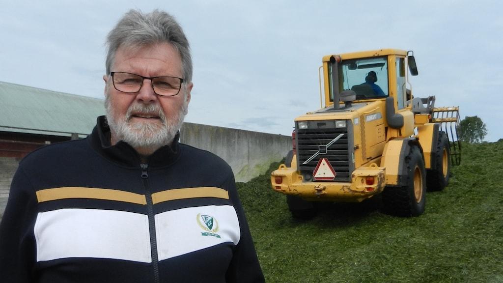 Erik Österve, mjölkbonde i Väse framför lastaren som jobbar med gräsklippet.