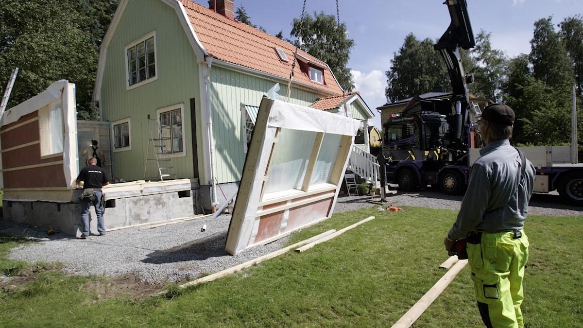 Arbetare gör en tillbyggnad på ett bostadshus.