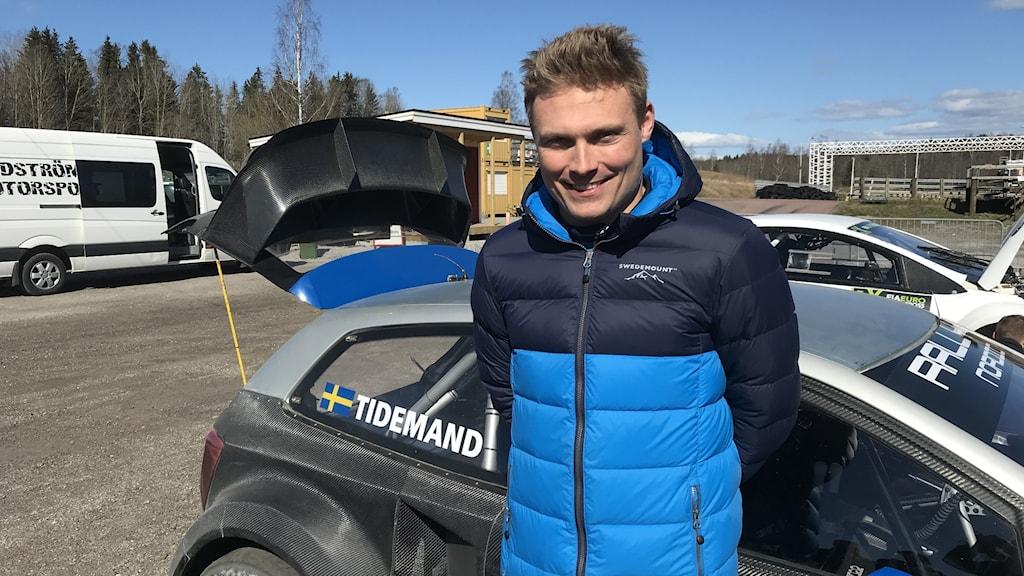 Pontus Tidemand står i blå jacka framför en svart rallycrossbil.