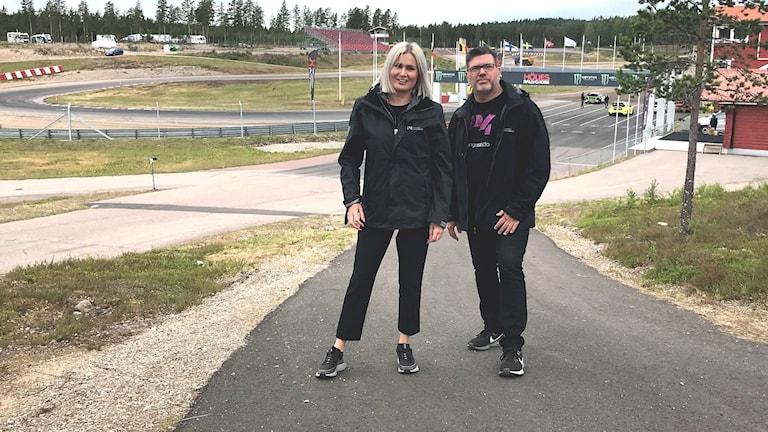 Sara Johansson och Bengt Höglind med rallycrossbana i bakgrunden. Foto: Henning Lymar/Sveriges Radio.