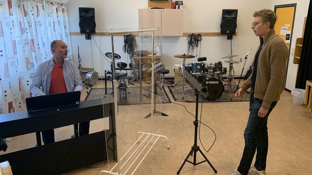 Peter Kronlöw som är sångpedagog och Felix Fougstedt som är kulturskoleelev har en coronasäkrad sånglektion med ett plexiglas mellan sig. Foto: Jonas Berglund/Sveriges Radio.
