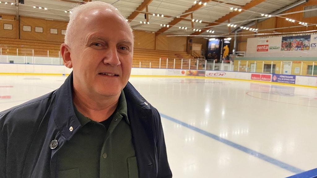 En man står med en ishockeyrink i bakgrunden.