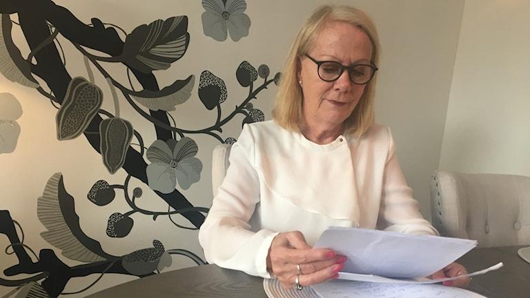 Elisabeth Björkman är faster till en funktionshindrad man som har gått miste om ett arv på grund av att överförmyndarhandläggaren i Arvika kommun godkänt ett felaktigt testamente. Hon sitter och tittar ner i papper, bakom sig har hon en tapet med blommor på. Foto: Jonas Berglund/Sveriges Radio.