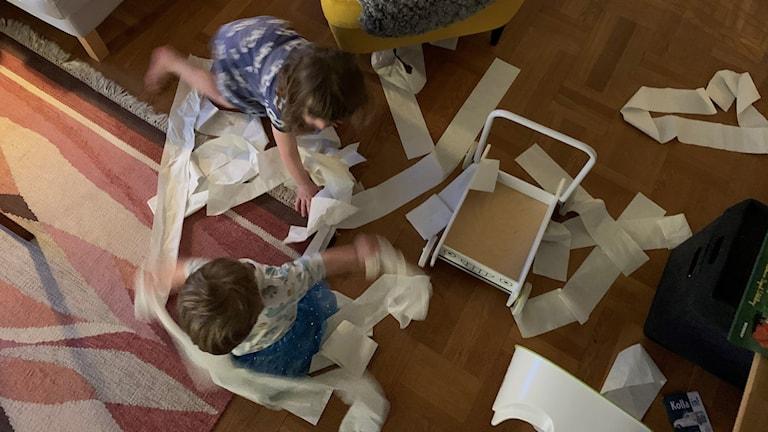 Två barn som leker med toalettpapper på vardagsrumsgolv.