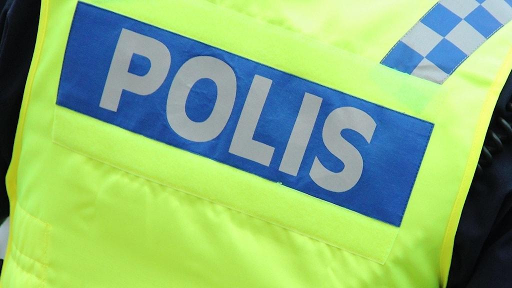 """En polisman i gul väst med texten """"polis"""". Foto: Lars-Gunnar Olsson/Sveriges Radio."""