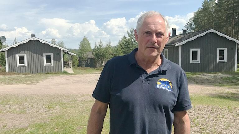 Hans Mallwitz på Björnbyn, gråa stugor i bakgrunden. Foto:Per Larsson/Sveriges Radio