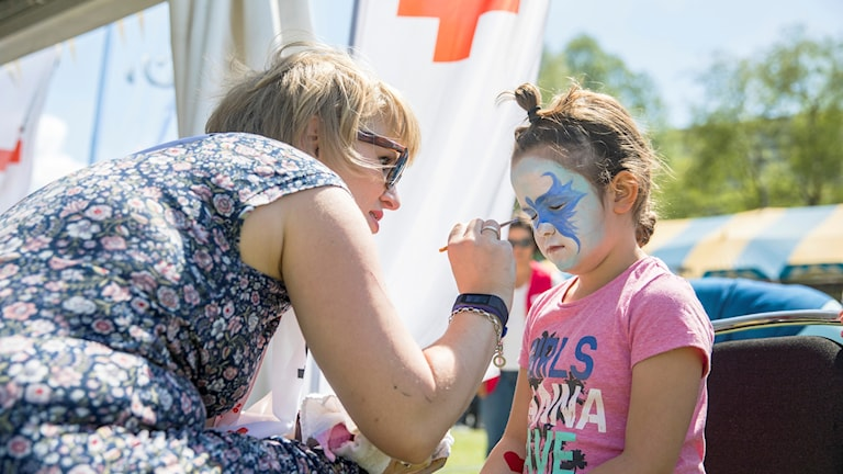 En kvinna från Röda Korset målar ett barn på nationaldagsfirande. Foto: Röda Korset