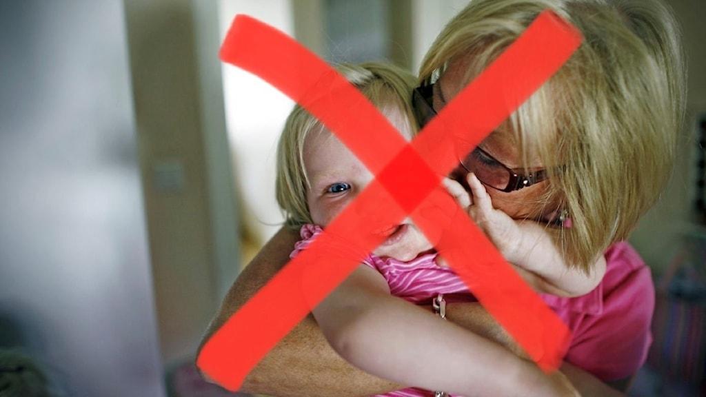 kvinna kramar barnbarn - men bilden är överkryssad med ett rött kryss