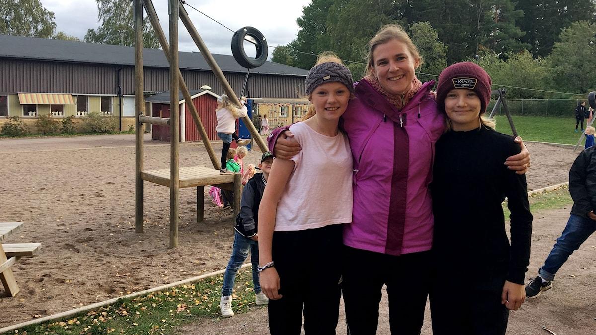 Kim Gustavsson idrottslärare tillsammans med eleverna Maja och Naemi