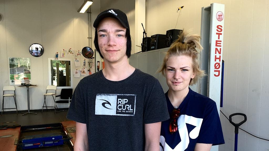En man och en kvinna, som står i en bilverkstad.