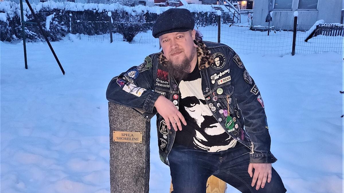 man sitter i snön med armbågen på en sten
