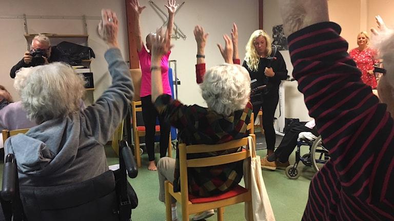 Äldre personer som sträcker upp händerna i luften.