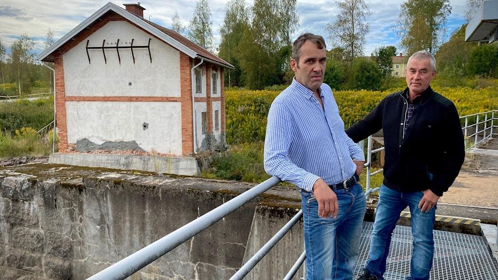 två män på bro framför kraftstation