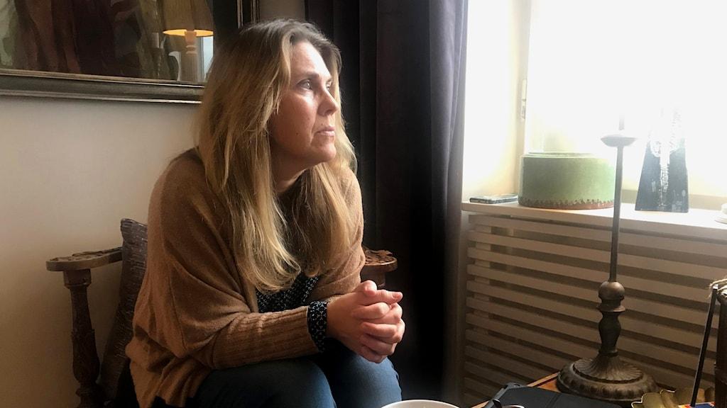 Kvinna sitter framför ett fönster och tittar ut. Ser ut som om hon längtar efter något.