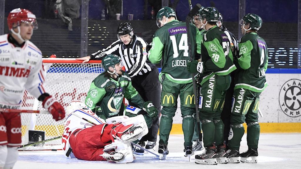 Flera hockeyspelare framför mål.