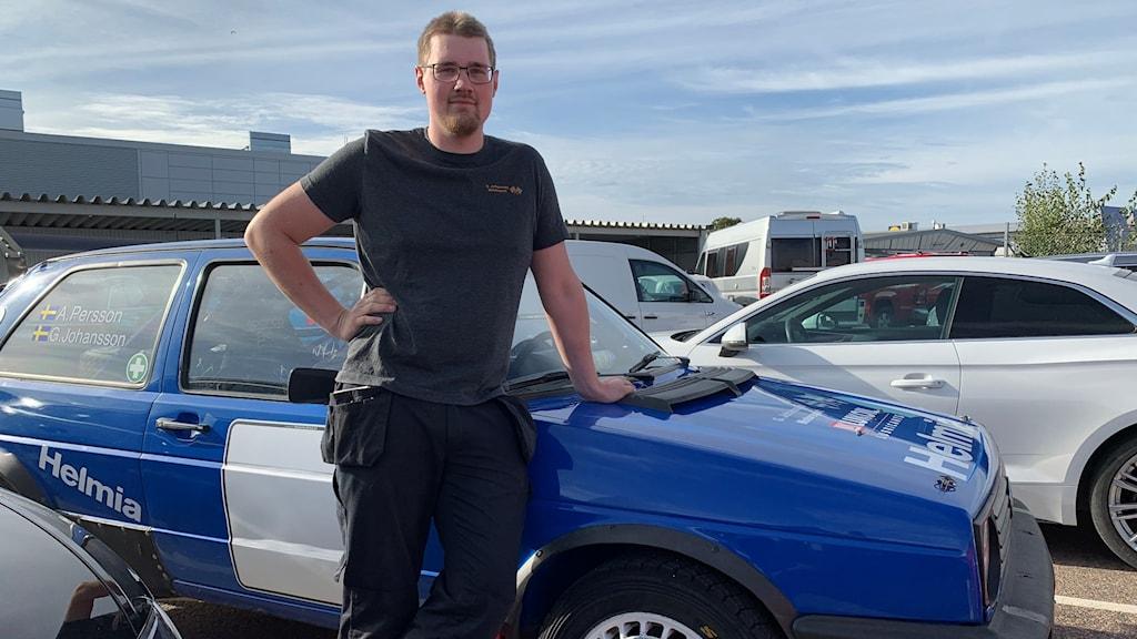 Gustav Johansson som är tävlingsledare och banchef står och lutar sig mot en bil