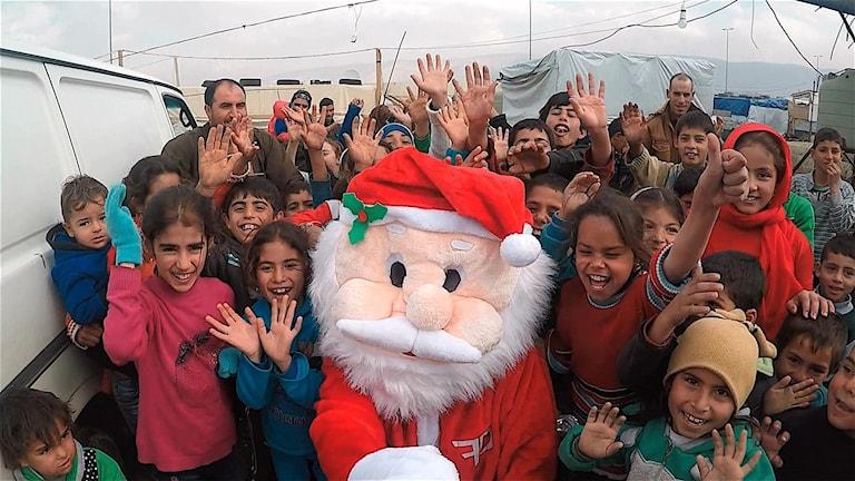 Tomten omgiven av barn syriska barn. Foto: Soleiman Andesh.