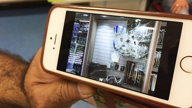 En mobil som visar en bild på sönderslagna saker i en butik. Foto: Elias Andersson/Sveriges Radio.