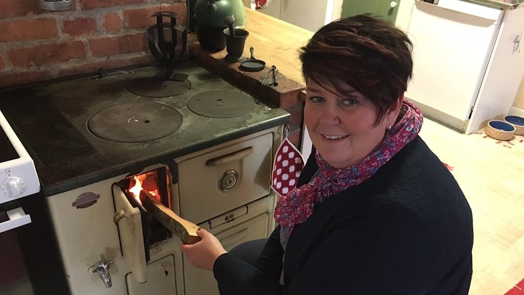 Kvinna lägger in vedklabbe i kökkspis