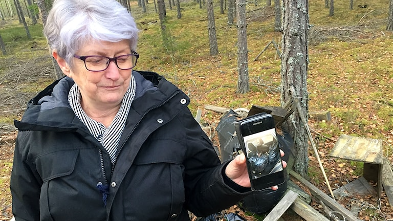 Åsa Gravander håller upp en bild av hennes bil där baksätet är fullt av sopsäckar.