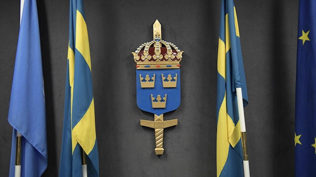 """Försvarsmaktens heraldiska vapen: """"I blått fält tre öppna kronor av guld, ordnade två och en. Skölden krönt med en kungl. krona och lagd över ett stolpvis stående svärd av guld"""