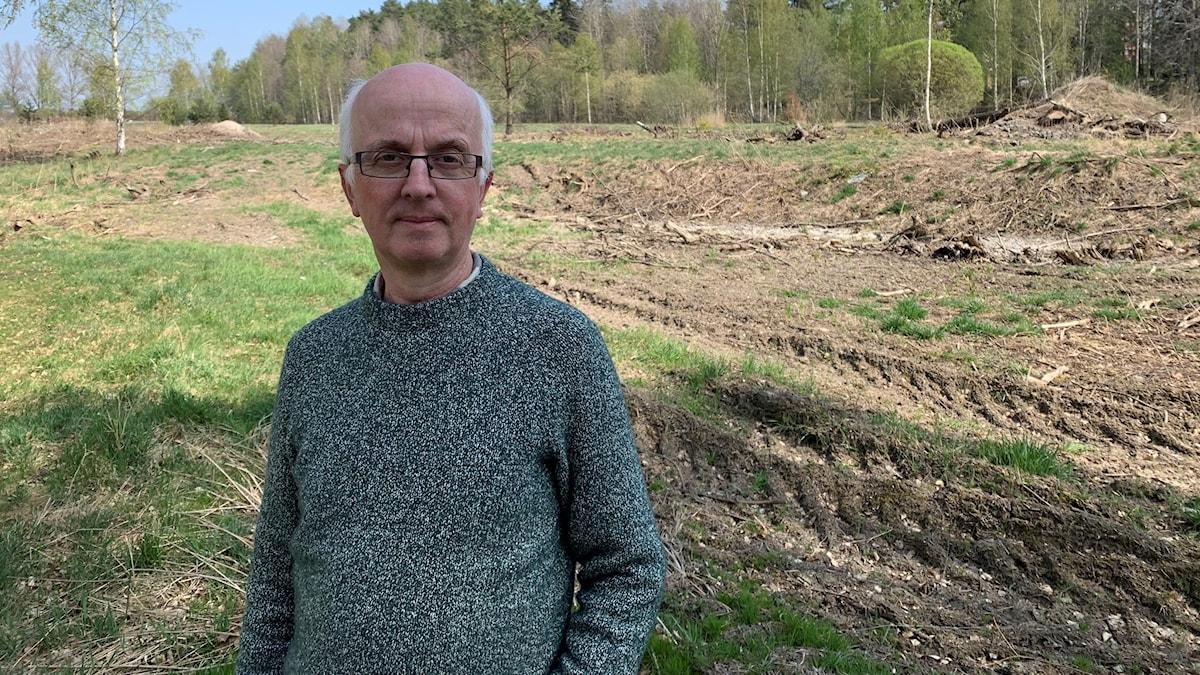 Gunnar Glöersen, syns långt fram i bilden och tittar in mot kameran. I bakgrunden syns natur, blandat brun jord och gräsmatta. Längst bak syns ett antal träd.