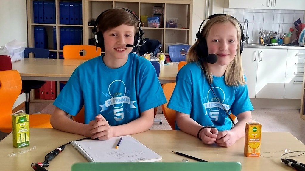 Två barn sitter i ljusblå tröjor vid en skolbänk.