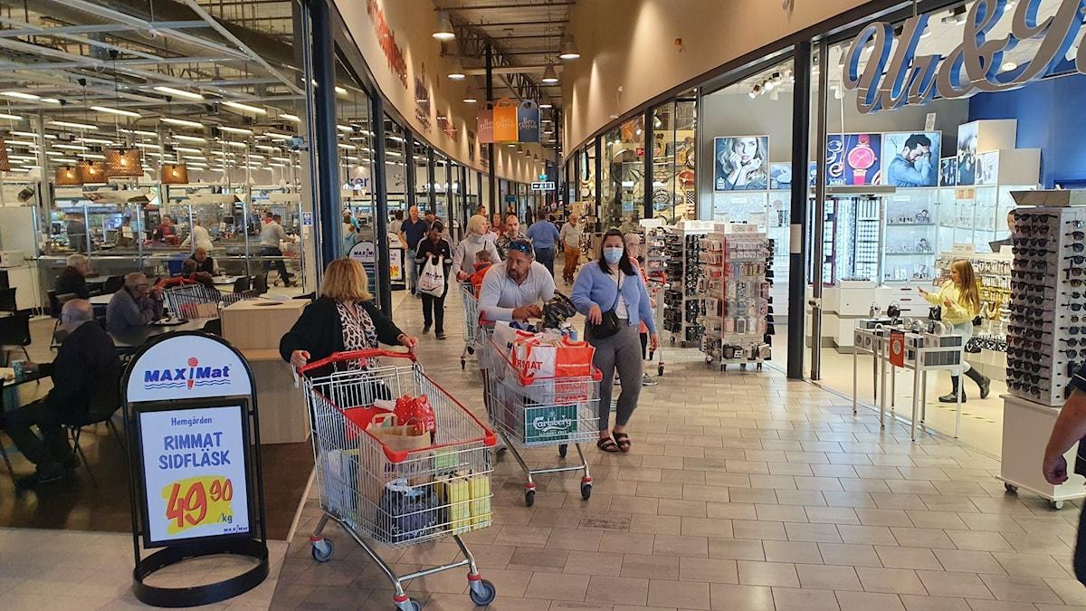 En shoppinggalleria, personer i munskydd med kundvagnar.