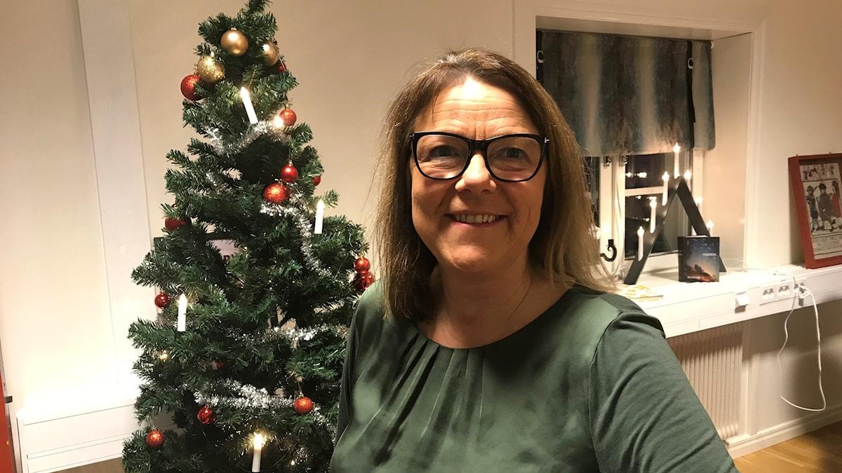 Anna-Lena Carlsson framför en julgran på ett kontor. Foto: Per Larsson/Sveriges Radio.