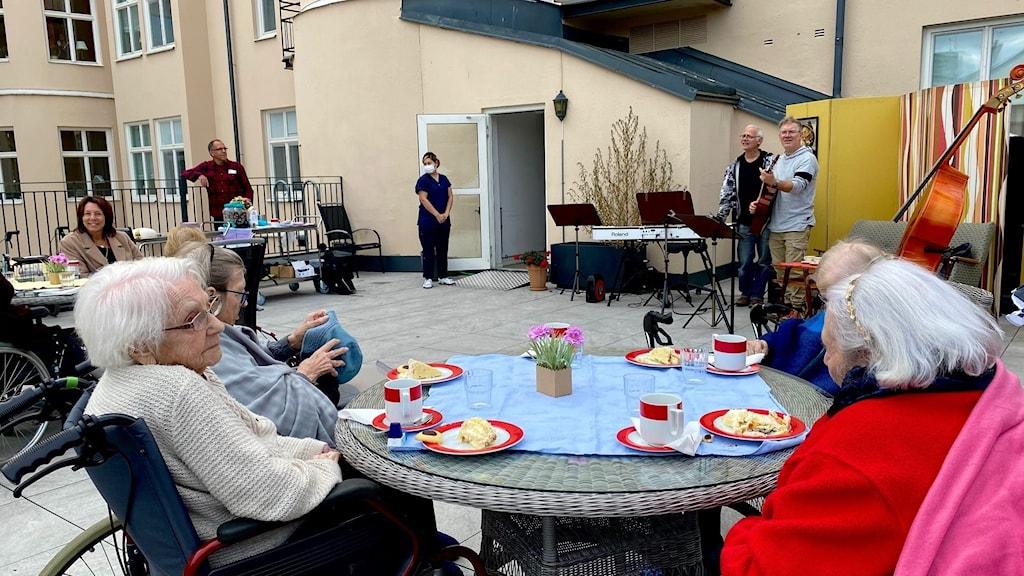 äldre kvinnor sitter i rullstol och äter fika vid bord.