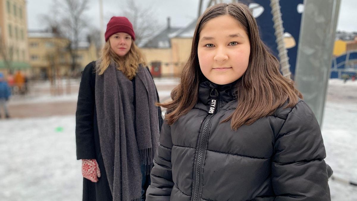En kvinna i mössa står bakom en flicka i svart jacka. Foto: Victoria Svärd Karlsson / Sveriges Radio