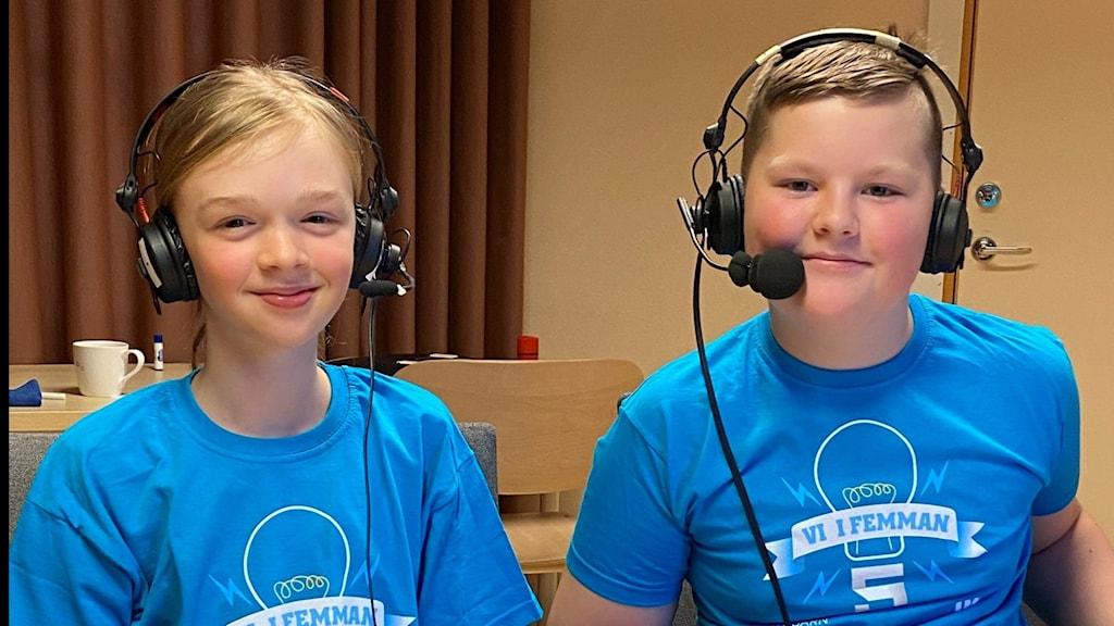 Två femteklasselever i blåa Vi i femman lagtröjor sitter vid ett bord och ser glada ut,
