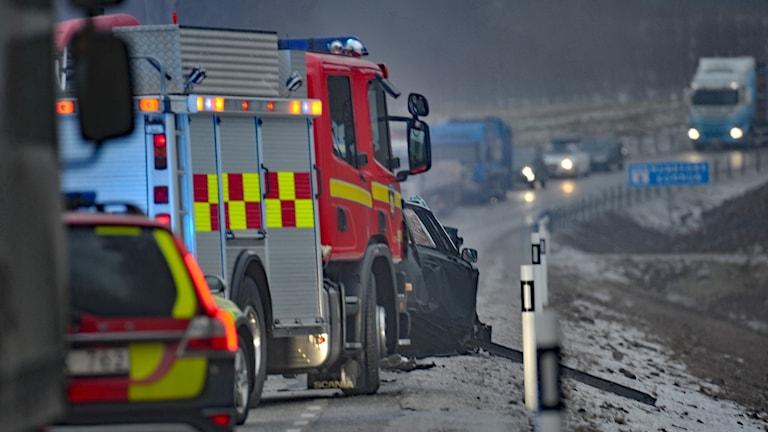 På fotot syns en krockad bil, en brandbil och en polisbil.