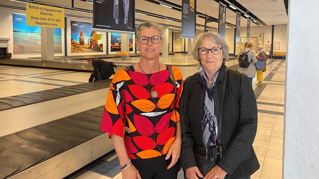 Två kvinnor vid ett bagageband på en färjeterminal.