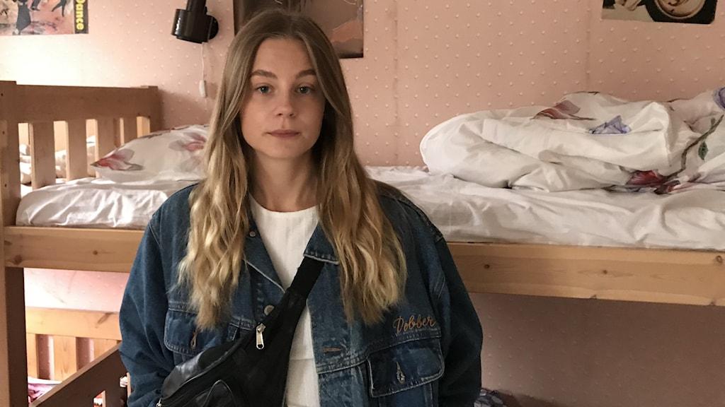 En ung kvinna står framför en obäddad våningssäng.