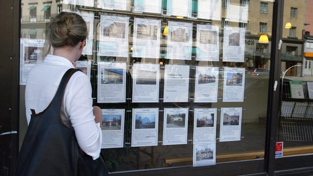 En kvinna tittar i en skyltfönster för fastigheter till salu.