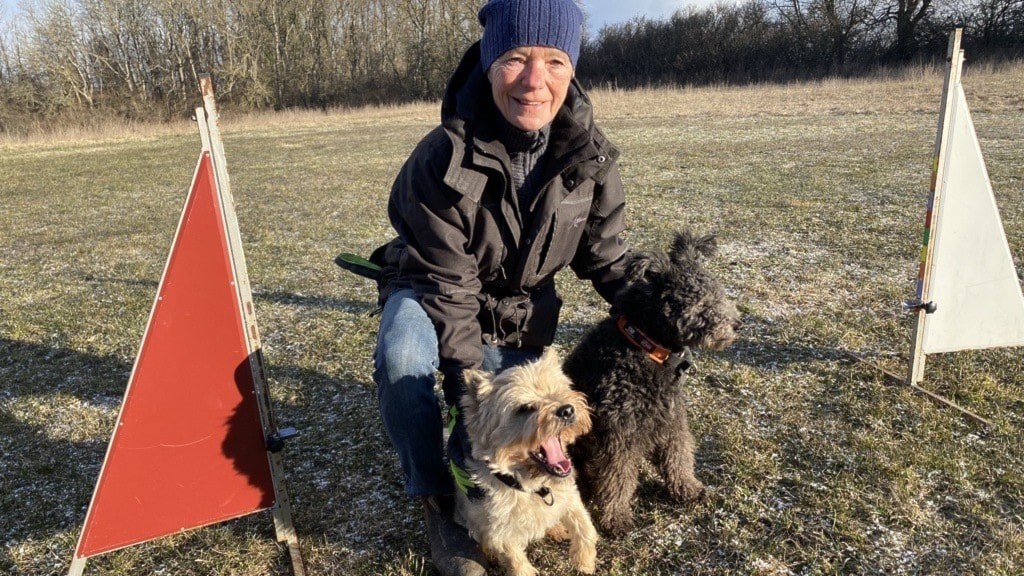 En kvinna sitter på ett knä med på en gräsmatta. Framför står två hundar.