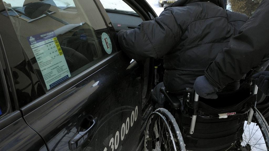 Person i rullstol stiger in i bil.