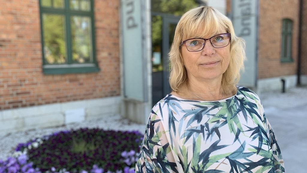 En kvinna i blommig tröja står utanför Region Gotlands kontor.