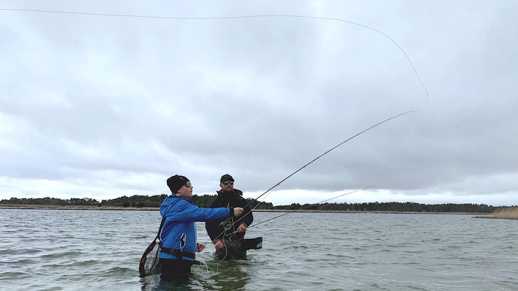 Två personer står i havet och kastar ett flugfiskespö.