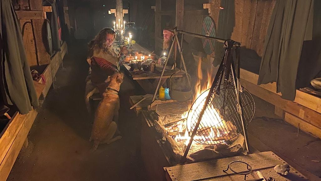 Två personer sitter tillsammans med en hund i ett stort rum med en öppen eld.