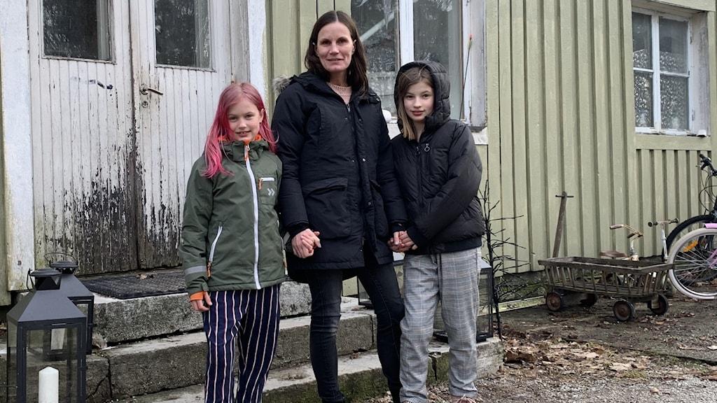 En kvinna och två barn står utanför ett hus.