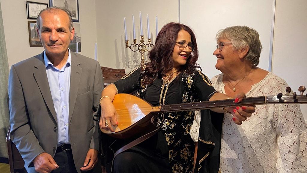 Josef Erdem, Suzanna Barmani och Christina Knutas står i ett vardagsrum. Suzanna har ett instrument i famnen.