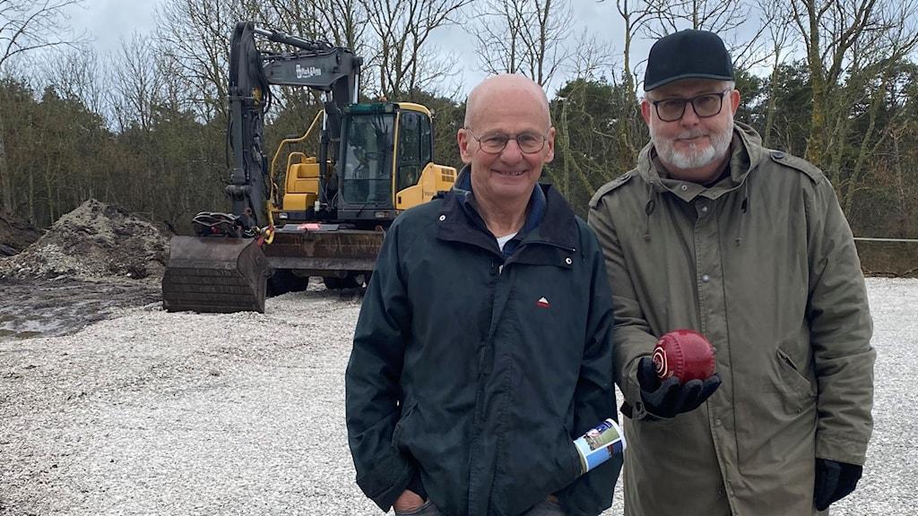 Två män står på en grusplan med klot - i bakgrunden står en grävare.