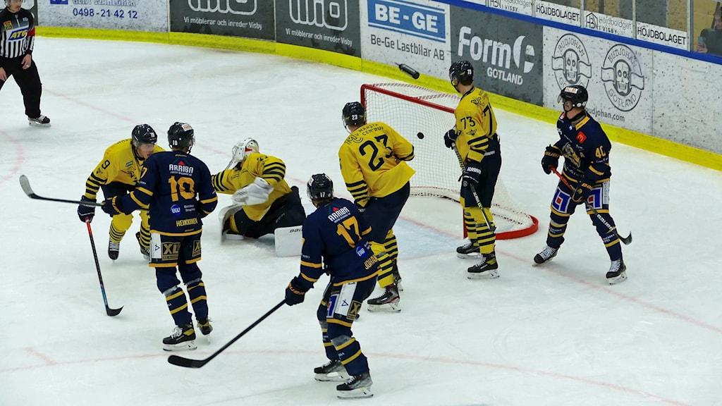 Ishockeymatch mellan lag i gula respektive blå dräkter. Trångt med spelare framför de gulas målvakt och det blir mål.