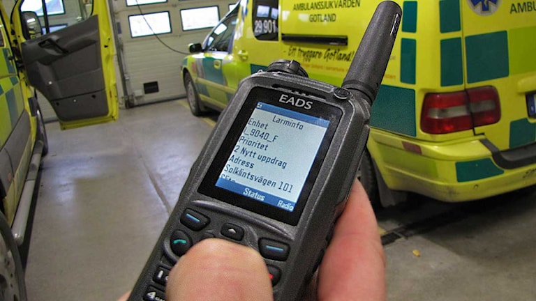 Larm i telefondisplay - ambulans i bakgrunden. Foto: Lasse Ahnell / SR Gotland