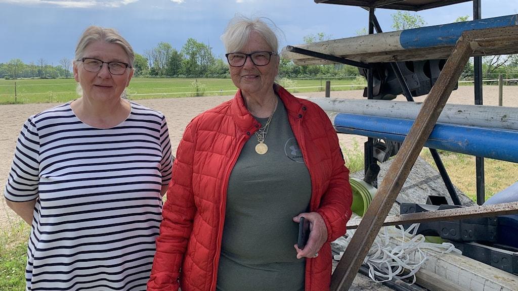 Två kvinnor står i en hästhage.
