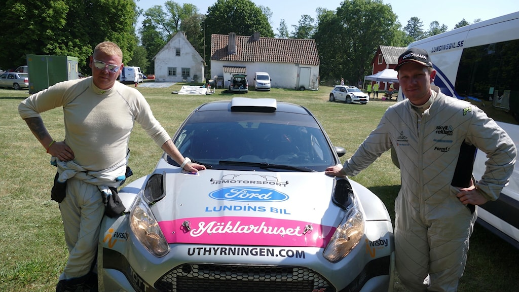 två män vid varsin sida av en rallybil.